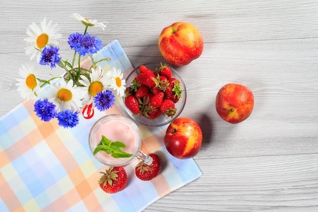 Erdbeerjoghurt in einem glas mit frischen erdbeeren, nektarine, kamille, kornblumen auf einem holztisch mit serviette draufsicht