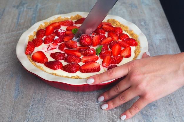 Erdbeerkäsekuchen mit basilikumblättern in einer roten keramikbackform. mädchen schneidet den kuchen. auf hölzernem hintergrund