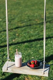 Erdbeerkaltpresssaft und erdbeeren auf einer schaukel