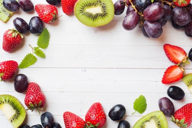 Erdbeerkiwitrauben der frischen frucht auf weißer tabelle mit kopienraum.