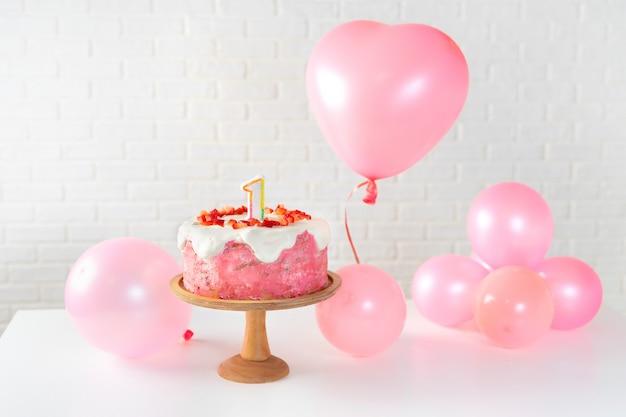 Erdbeerkuchen und rosa ballons auf weißem hintergrund