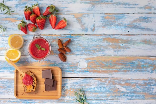 Erdbeermarmelade auf hölzernem hintergrund