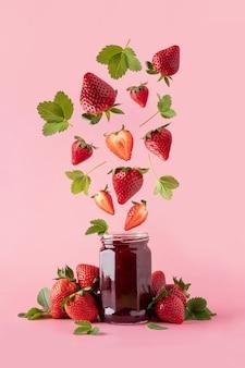 Erdbeermarmelade im glas und fallende erdbeerstücke. erdbeer-levitation. schwebebeeren auf rosa hintergrund.