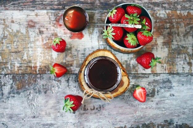 Erdbeermarmelade im glas und frische erdbeeren.