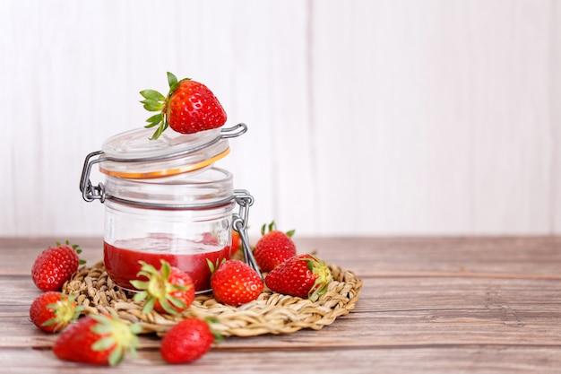 Erdbeermarmelade in einem glas auf hölzernem hintergrund
