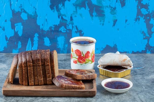 Erdbeermarmelade mit scheibe schwarzbrot und tasse tee.