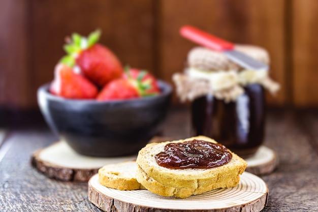 Erdbeermarmeladen-toast mit erdbeeren in der oberfläche