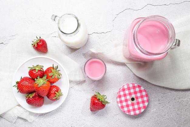 Erdbeermilch-shake-krug, erdbeeren und milch auf weißem hintergrund