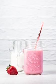 Erdbeermilch-shake-krug mit stroh, erdbeere und milch auf weißem hintergrund