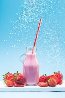 Erdbeermilch-shake-krug mit stroh, erdbeeren und fliegendem zucker auf blauem hintergrund
