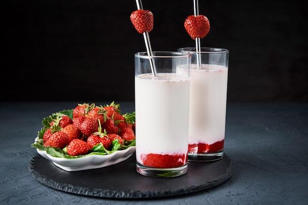 Erdbeermilch-smoothie im glas mit stroh auf einer dunklen