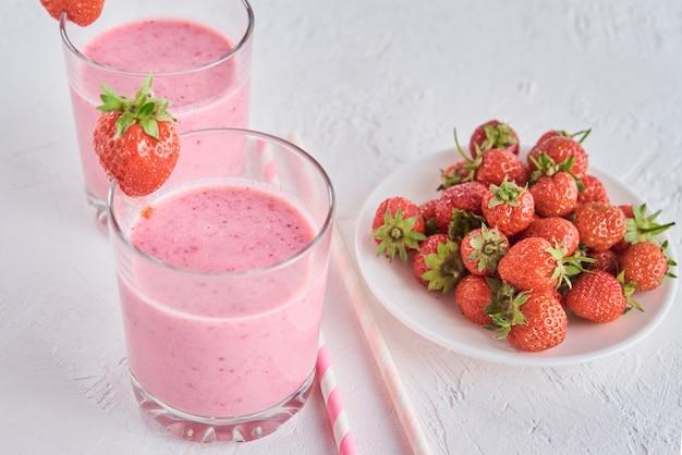 Erdbeermilchshake im glas mit stroh und frischen beeren auf weiß