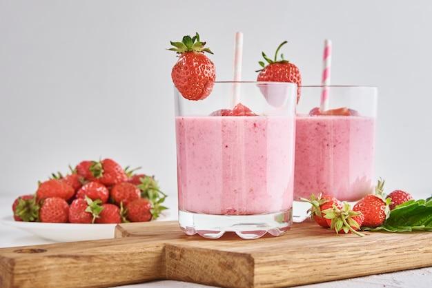 Erdbeermilchshake im glas mit stroh und frischen beeren auf weißem hintergrund