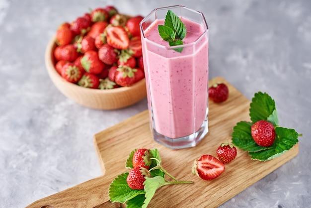 Erdbeermilchshake im glas und frische erdbeeren mit blättern