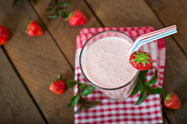 Erdbeermilchshake smoothie mit frischer erdbeere auf einem holztisch