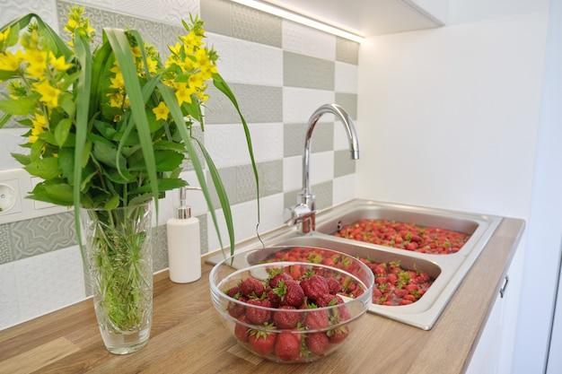 Erdbeersaison, beeren in wasser im waschbecken zu hause waschen. viele erdbeeren, beeren für marmelade vorbereiten, zum einfrieren
