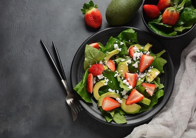 Erdbeersalat mit spinat, feta, avocado, balsamico-essig und olivenöl auf einem teller