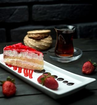Erdbeersirup-vanillepudding-biskuitkuchen und eine tasse aromatisierten tee