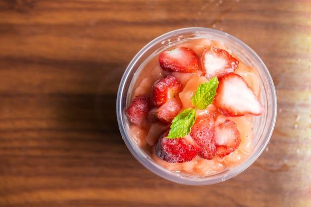 Erdbeersmoothies in der plastikschale. gesundes getränk der erfrischung. ansicht von oben.