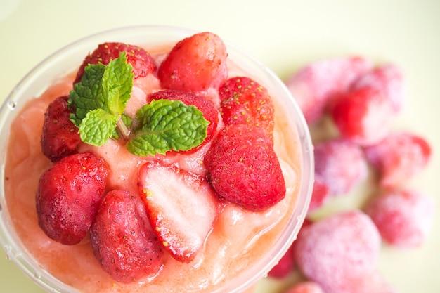 Erdbeersmoothies in der plastikschale. gesundes getränk der erfrischung.