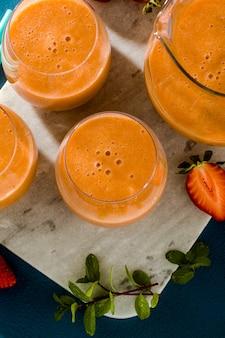 Erdbeersmoothies in einer karaffe und in den gläsern auf einem blauen hintergrund. rohes frühstück