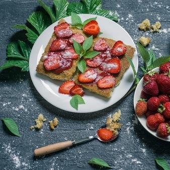 Erdbeertoast mit minze und marmelade auf grauer zementhintergrund draufsicht.
