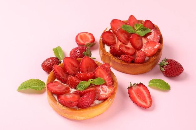 Erdbeertörtchen auf rosa hintergrund, nahaufnahme.