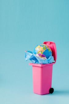 Erdkugel liegt im müll. der globus liegt in einem plastikhaufen. plastikverschmutzung der natur