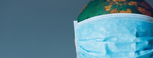 Erdkugel mit gesichtsmaskenschutz. universelles medizinisches konzept für coronaviren