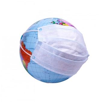 Erdkugel mit schutzmaske steht gegen die blaue miniatur des virus. coronavirus, covid-19-konzept.