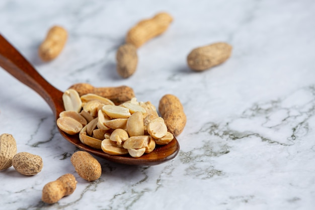 Erdnüsse im holzlöffel auf weißem marmorboden