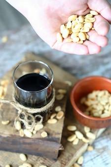 Erdnüsse in der hand und schwarzes soda mit erdnüssen.