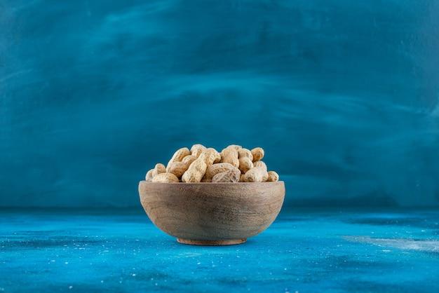 Erdnüsse in der schale in einer schüssel auf der blauen oberfläche
