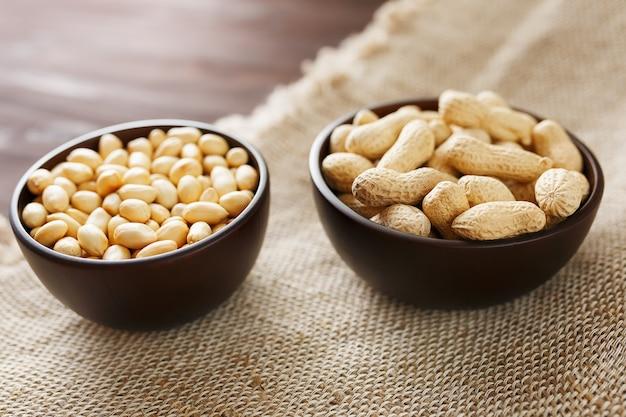 Erdnüsse in der schale und geschälte nahaufnahme in tassen, geröstete erdnüsse in der schale und geschält gegen ein braunes tuch