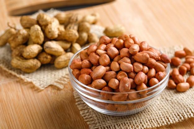 Erdnüsse in der schüssel auf dem hölzernen hintergrund.