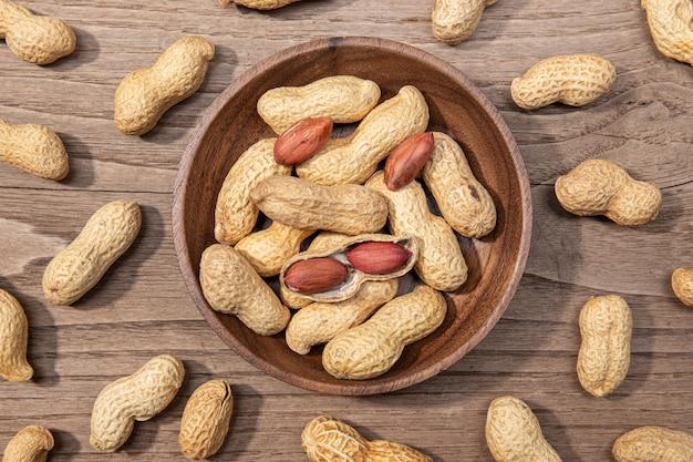 Erdnüsse in der schüssel auf rustikalem holztisch. arachis hypogaea