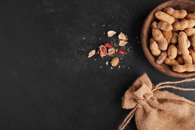 Erdnüsse in einer hölzernen tasse auf schwarzer oberfläche, draufsicht.