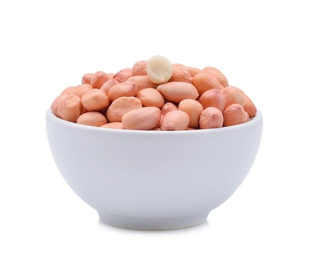 Erdnüsse in einer holzschale auf weiß