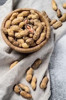 Erdnüsse in einer schale. bio rohe erdnuss. grauer hintergrund. draufsicht. platz für text