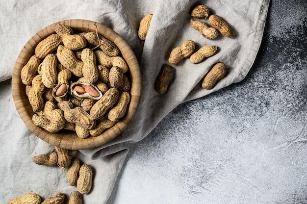 Erdnüsse in einer schale. vegetarisches essen. grauer hintergrund. draufsicht. platz für text