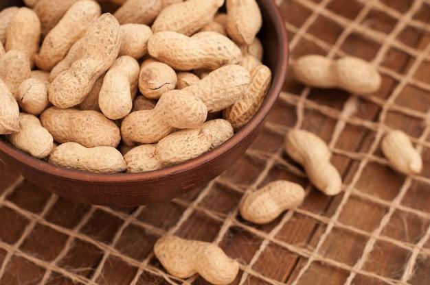 Erdnüsse in einer schüssel auf einem garngitter. brauner hölzerner hintergrund