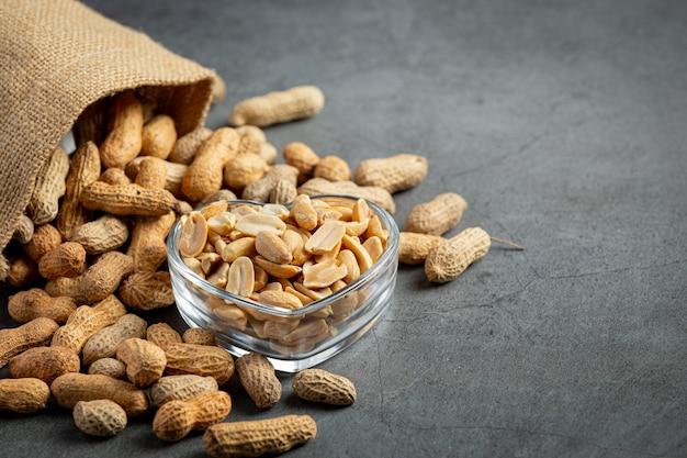 Erdnüsse in herzförmiger platte neben einen sack erdnüsse