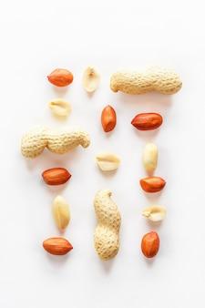 Erdnüsse lokalisiert auf weißem hintergrund. geschälte schale und scarlup.