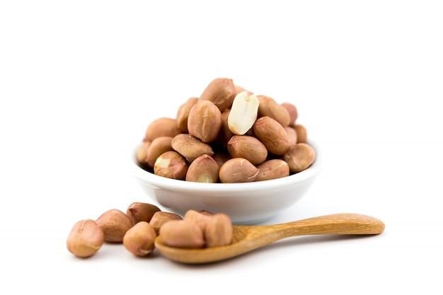 Erdnüsse und holzlöffel isoliert