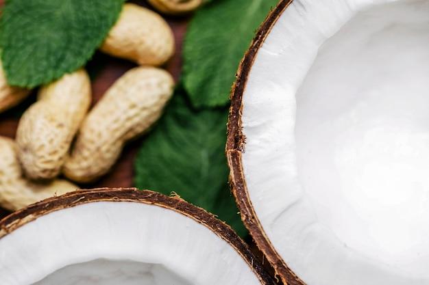 Erdnüsse und kokosnuss liegen auf grünen blättern