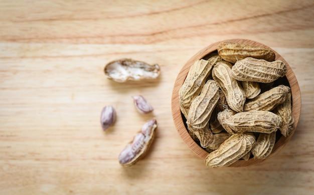 Erdnuss in der draufsicht der hölzernen schüssel und des holzes / gekochte erdnüsse