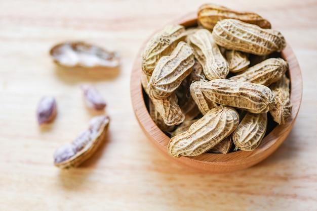 Erdnuss in der hölzernen schalenschüssel und in der hölzernen draufsicht