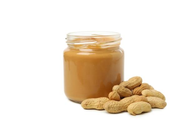 Erdnuss und glas mit erdnussbutter lokalisiert auf weißem hintergrund