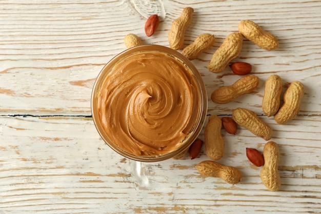Erdnuss und schüssel mit erdnussbutter auf hölzernem hintergrund