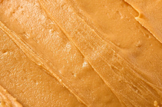 Erdnussbutter als hintergrund. ein traditionelles produkt der amerikanischen küche
